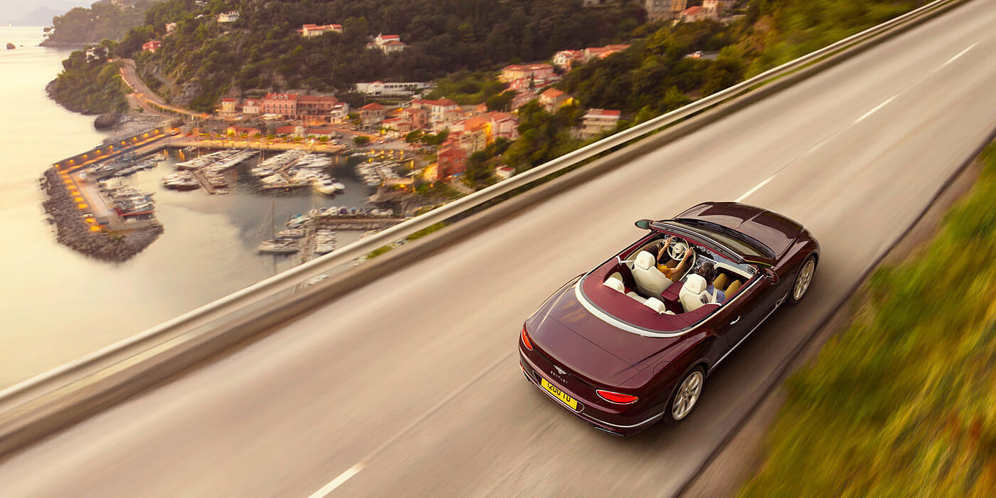 NEW-DARK-RED-BENTLEY-CONTINENTAL-GT-CONVERTIBLE-DRIVING-NEAR-ITALIAN-SEASIDE-TOWN